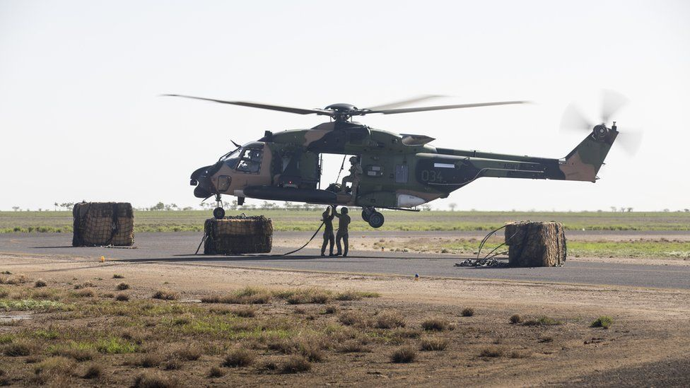 Australian defence staff load a helicopter with hay bales in northern Queensland's cattle region
