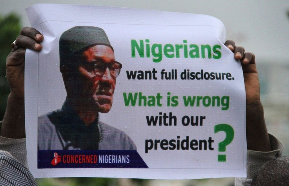 """A Nigerian protester pictured on 7 August 2017 shows a placard reading, """"Nigerians want full disclosure. What is wrong with our president?"""""""
