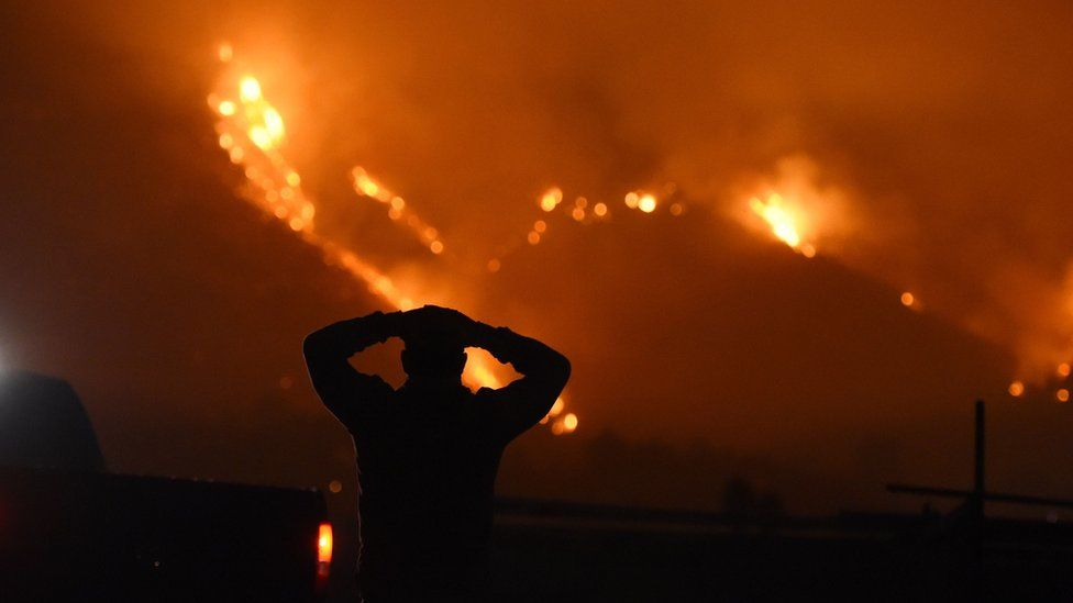 Man stands watching the fire burn