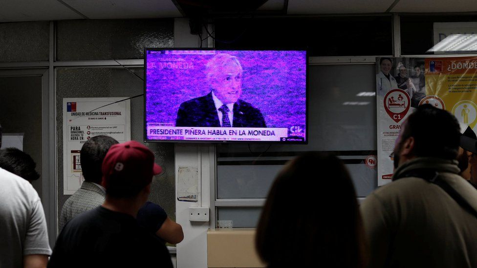 People watch a television broadcasting a speech by Chile's President Sebastian Pinera in an emergency room of a hospital amid anti-government protests in Santiago, Chile, 12 November, 2019