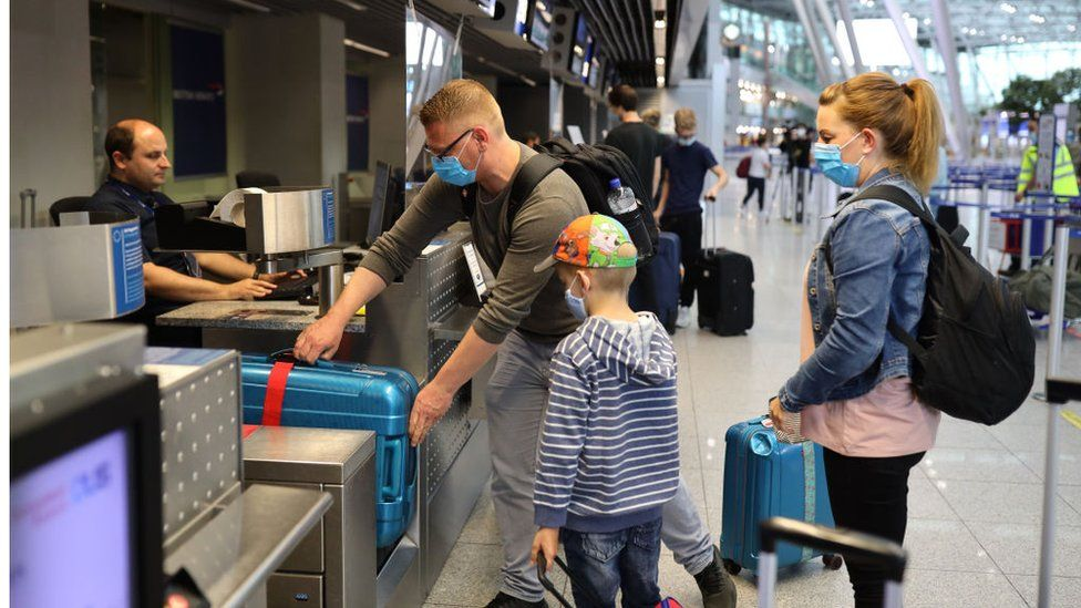 Tourists wait to check in for a Tui flight at Dusseldorf Airport