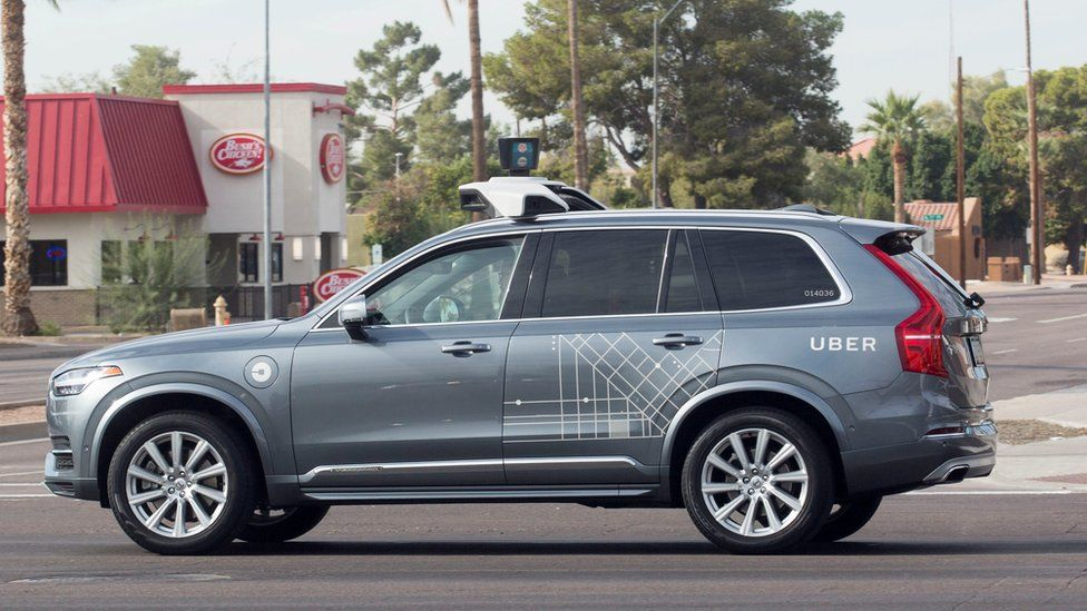 A metallic grey Volvo car, wrapped with some occasional Uber branding in white vinyl, is seen here with a large mount on top of the vehicle which houses self-driving equipment