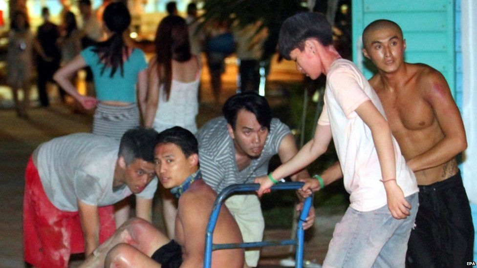 Taiwanese push a young man suffering from burns to his legs to an ambulance at the Formosa Fun Coast park in the Bali District of New Taipei City, northern Taiwan, 27 June