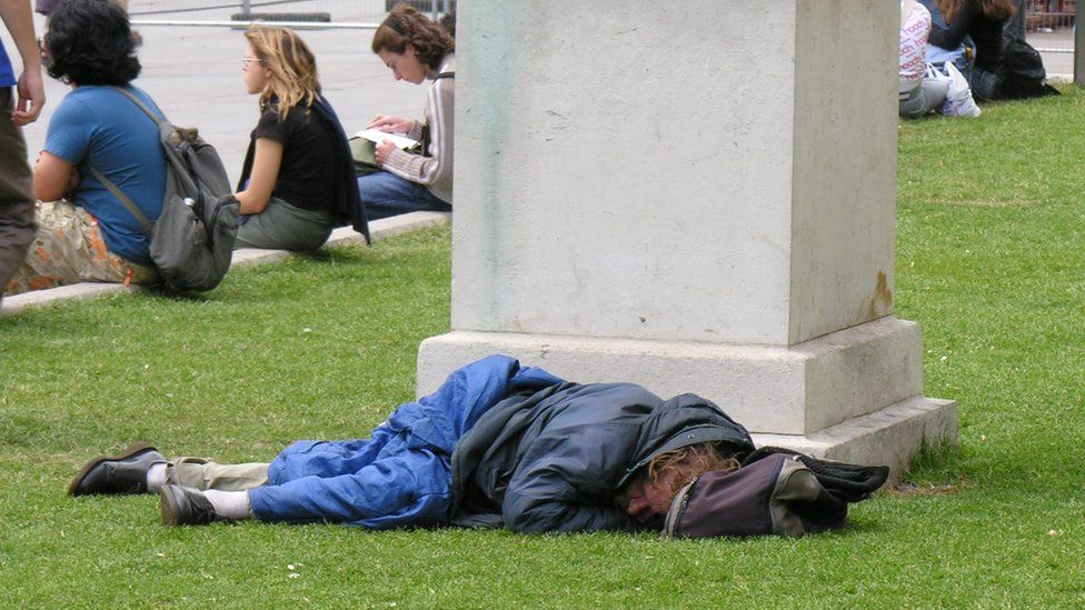 A homeless man asleep in a park