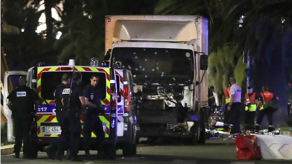 Police officers and rescue workers stand near a van that ploughed into a crowd leaving a fireworks display in the French Riviera town of Nice on July 14, 2016.