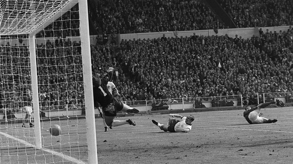 Geoff Hurst scoring England's controversial third goal as West Germany goalkeeper Hans Tilkowski dives for the ball during the World Cup Final on 30 July, 1966