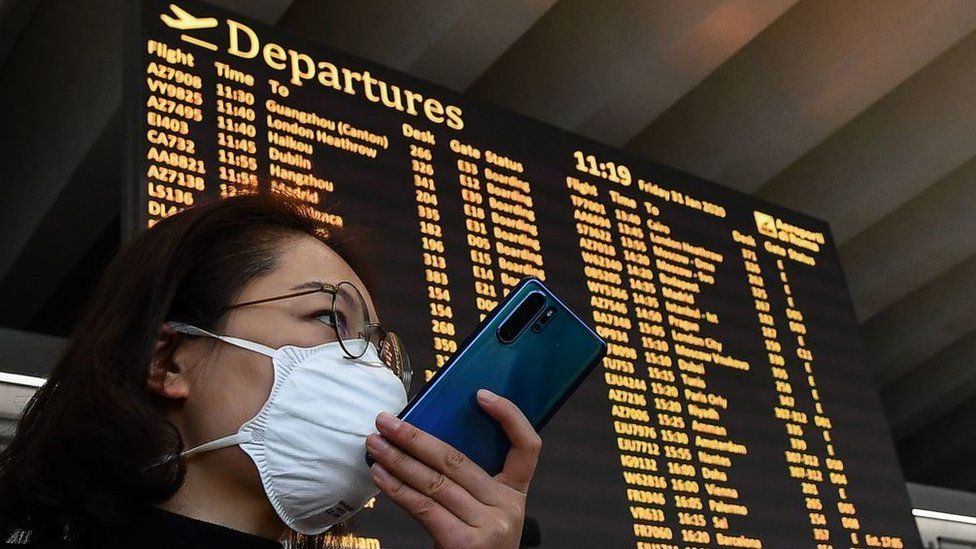 A passenger wearing a respiratory mask speaks on her smartphone by the departures board on January 31, 2020 at Rome's Fiumicino airport
