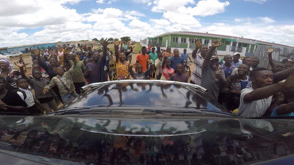 People crowd around car
