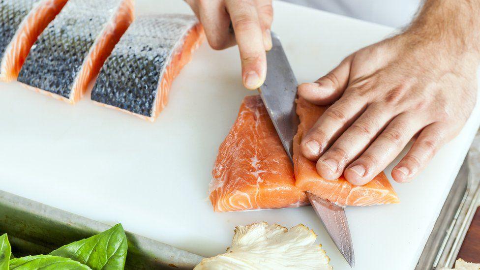 Cutting raw salmon