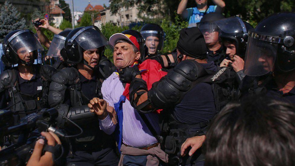 Police grab a protester in Romania