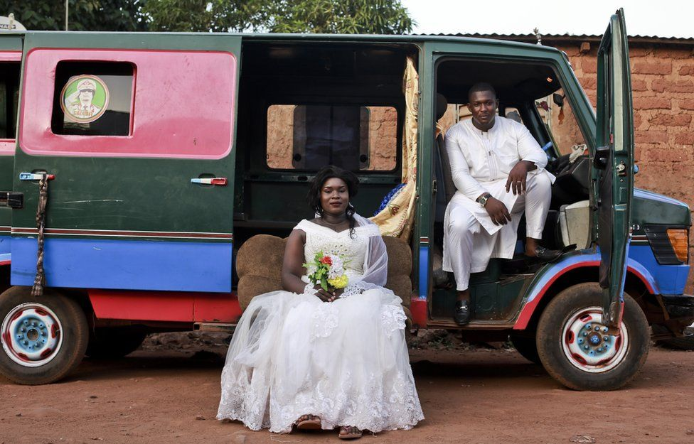 A groom and bride pose in front of a colourful mini van