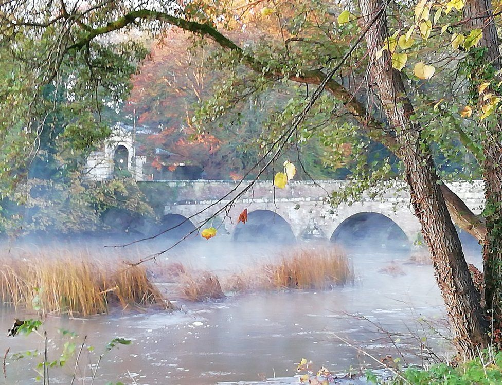 Mist over water by a bridge