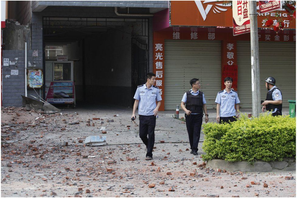 Police investigators inspect the area around a damaged building a day after a series of blasts in Liucheng county in Liuzhou, south China's Guangxi province on 1 October 2015.
