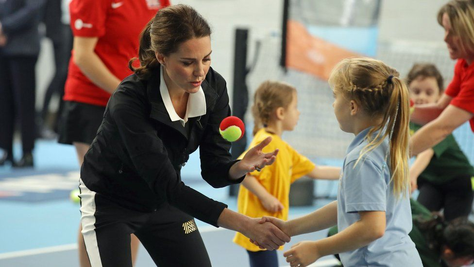 The Duchess of Cambridge throws a tennis ball with a girl