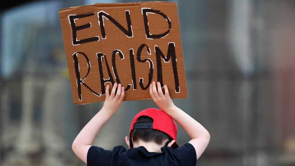 A child hold an 'end racism' sign