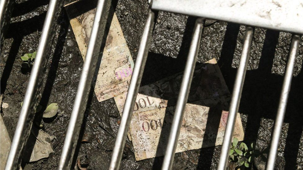 100-bolivar notes lie discarded in the gutter