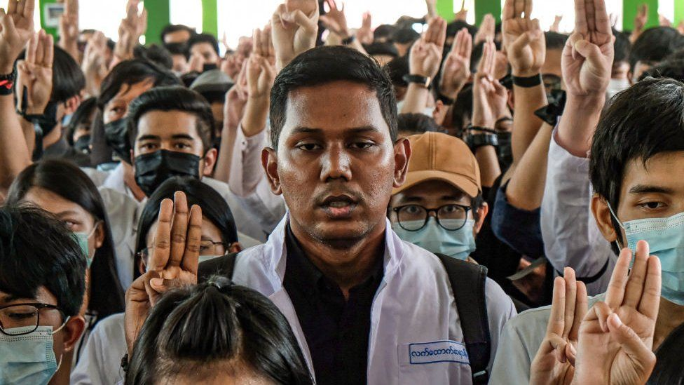 Medical students hold up the three finger salute at the funeral of Khant Nyar Hein in Yangon, Myanmar on March 16, 2021