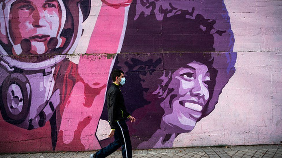 A man wearing a mask walks past a feminist mural in Madrid