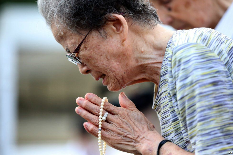 A woman cries as she offers prayers at the Peace Park before the 70th anniversary of the Nagasaki bombing - 9 August 2015