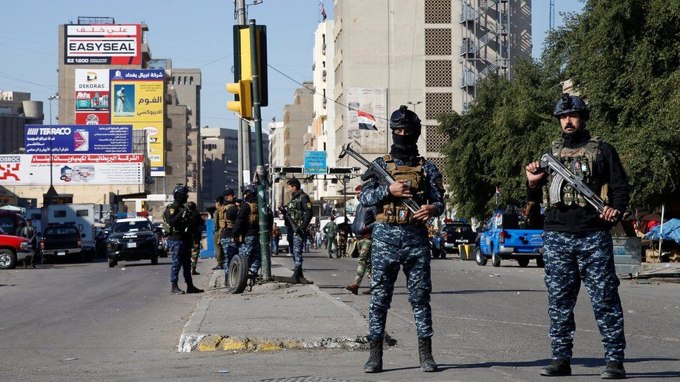 Iraqi security forces stand near the scene of a twin suicide bomb attack in Baghdad on 21 January 2021