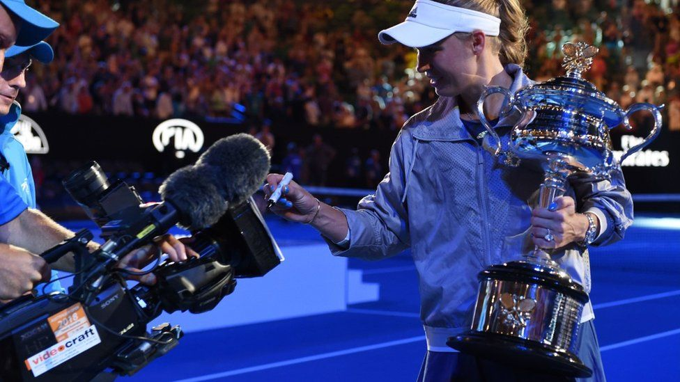Caroline Wozniacki signs her autograph on a TV camera after winning the Australian Open tennis tournament in Melbourne on January 27, 2018.