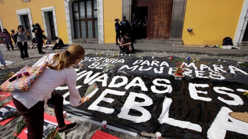 "A woman places flowers during a vigil in Puebla. The sign reads ""Justice for Mara"" and ""Women killed in Puebla"". (17/09/2017)"