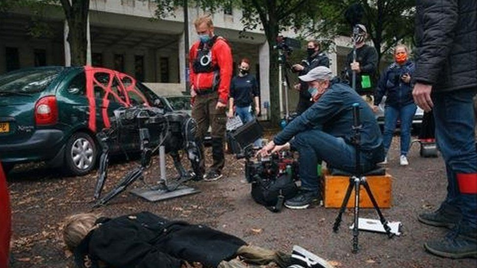An actor lies on the floor in a chaotic street scene, with the camera operator and crew wearing masks