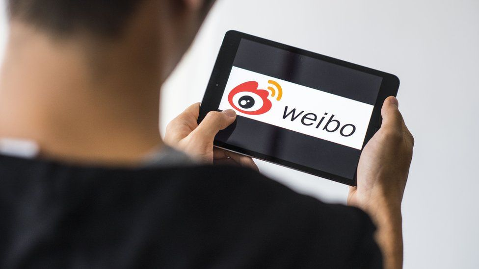 A man uses the Sino Weibo social media platform on a mobile device