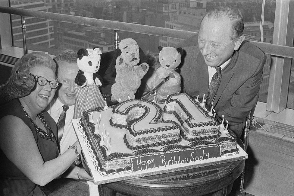 Harry Corbett and his wife Marjorie with Sooty, Sweep and Soo and a birthday cake on Sooty's 21st birthday in 1969