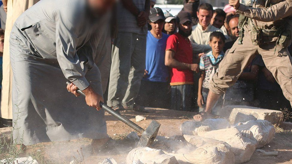 A photo published by Islamic State purportedly showing a militant destroying statues looted from the ancient ruins of Palmyra in Syria (2 July 2015)