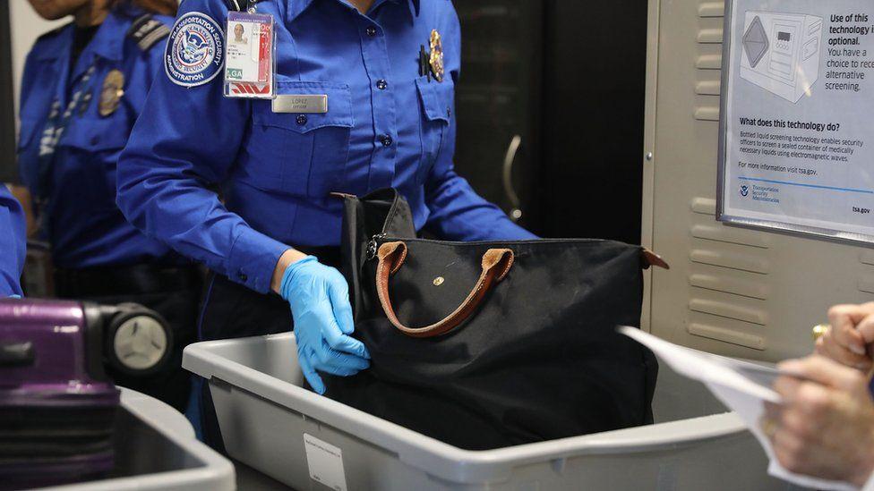 An anonymous TSA official checks a bag in a luggage tray