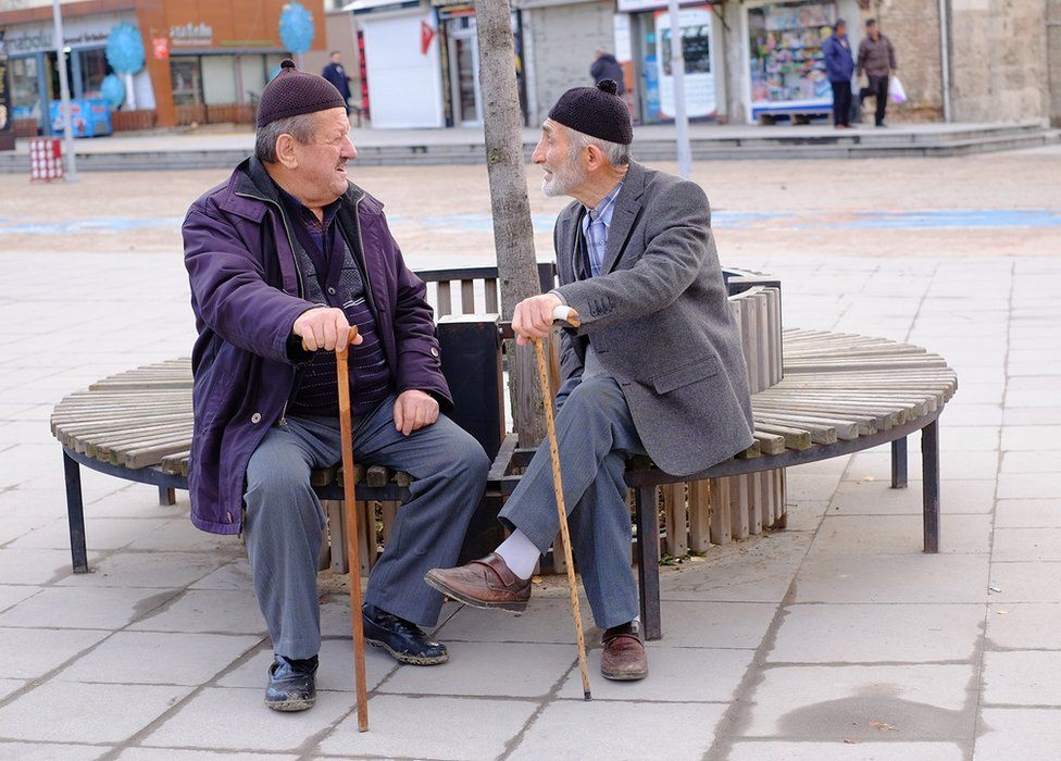 Two people sit on a bench to have a conversation
