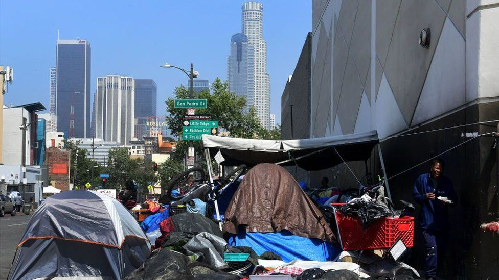 Tents with skyscrapers in the background in Los Angeles