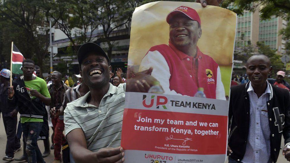 Supporters of President Uhuru Kenyatta hold a poster bearing a picture of Kenyatta as they celebrate on November 20, 2017 in Nairobi