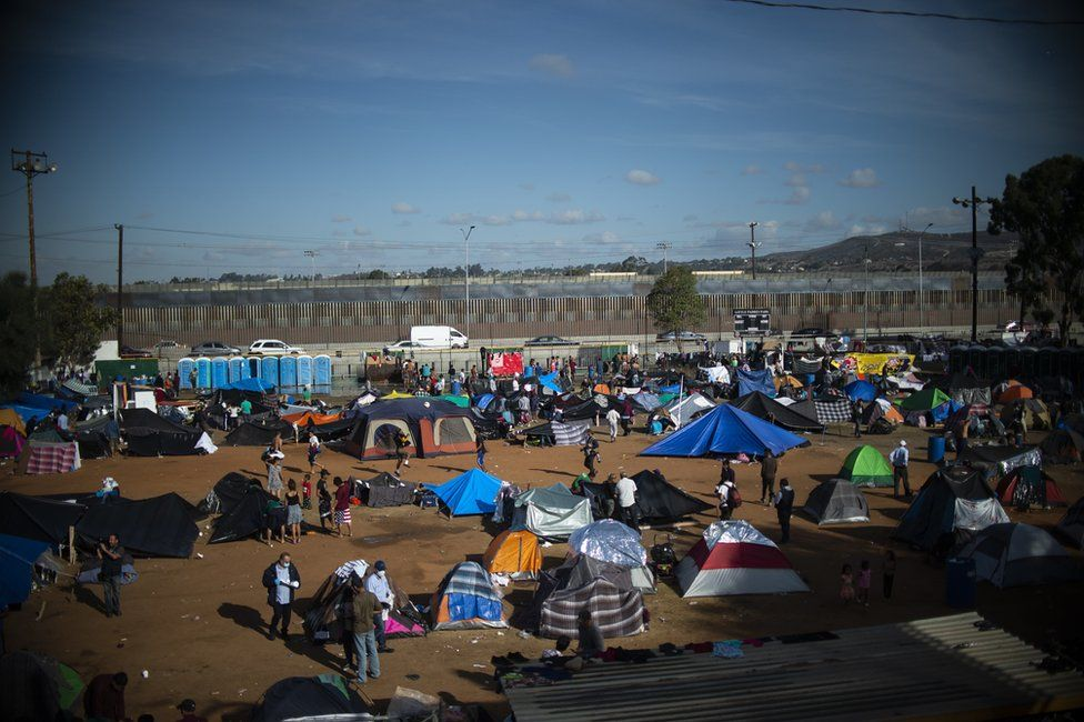 Central American migrants, mostly Hondurans, remain at a shelter near the US-Mexico border fence in Tijuana, 23 November