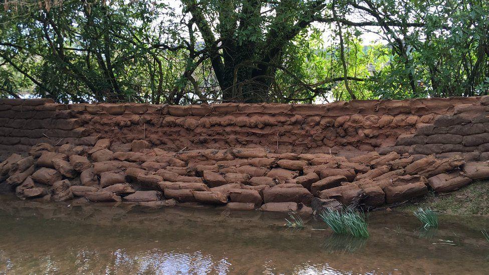 A breached sandbag wall