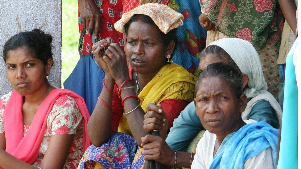 Women tea workers listen as an unseen NGO worker speaks