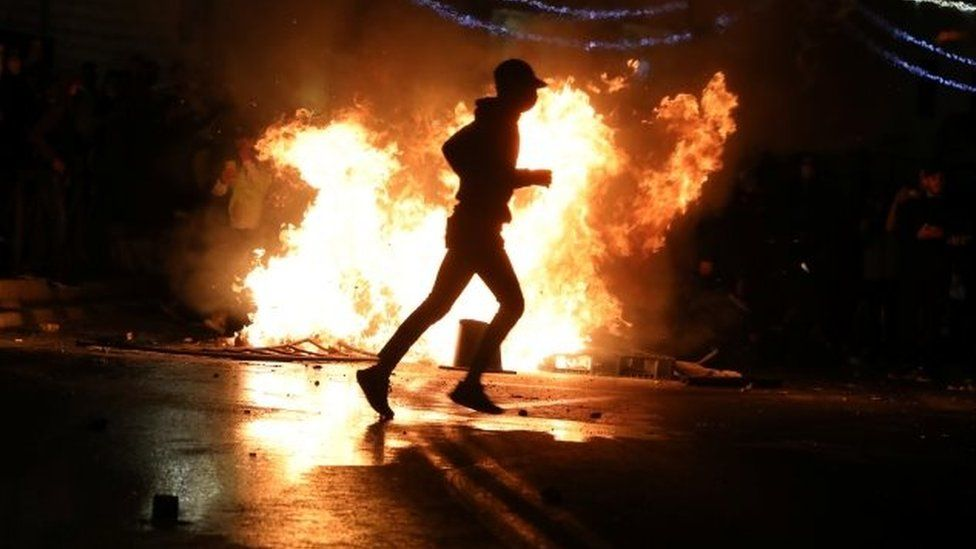A protester runs in front of a burning barricade in Jerusalem, Israel. Photo: 22 April 2021