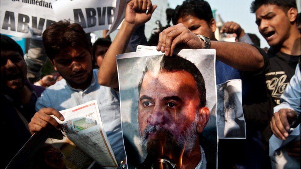 Protesters burn a photograph of Tarun Tejpal