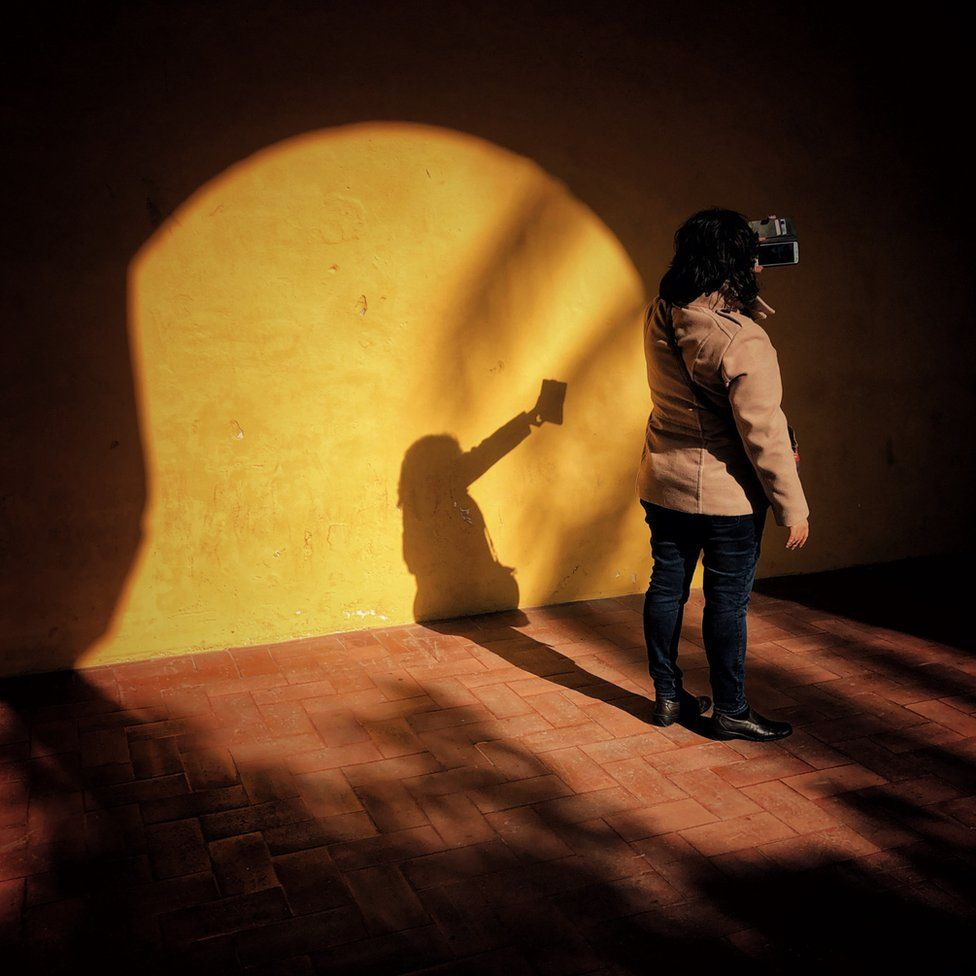 A woman takes a picture of herself as the sun shines through the archway she stands under