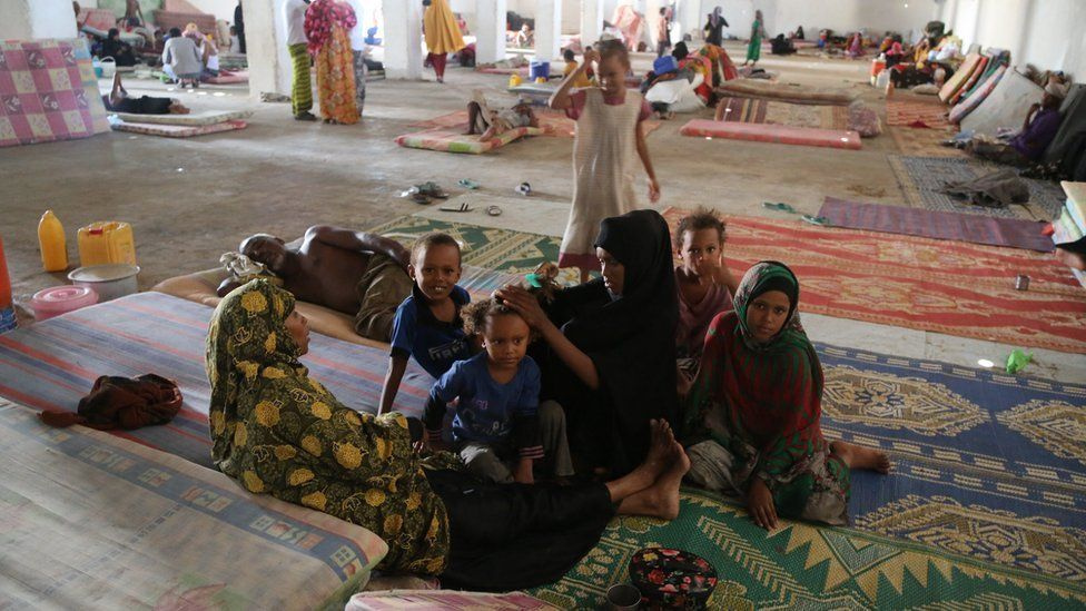 People sitting on a mattress at a transit centre, Bossasso, Somalia