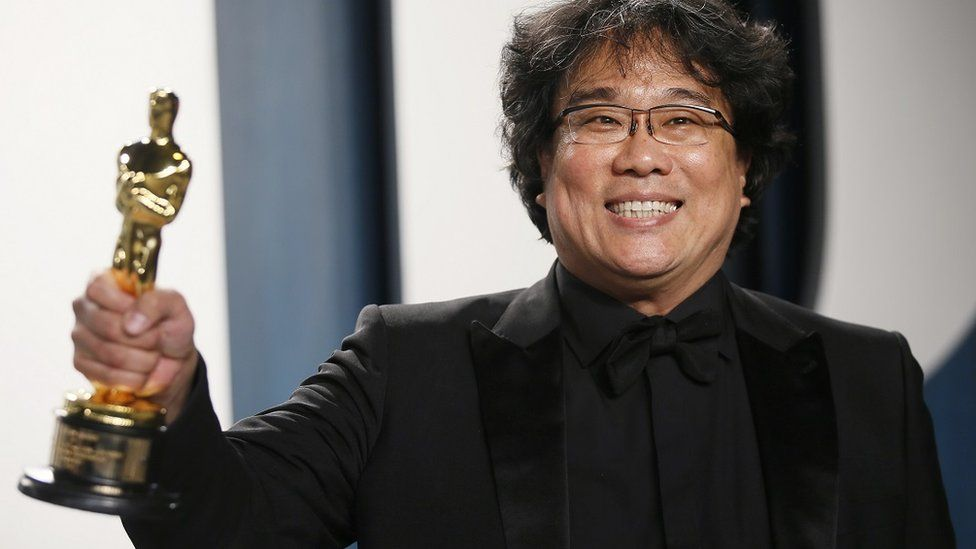 Bong Joon Ho hlds one of his Oscars