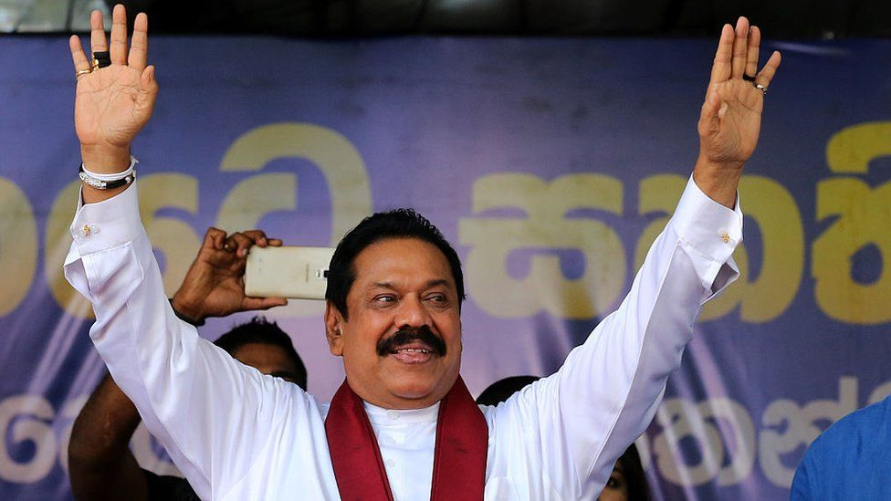 Mahinda Rajapaksa waves to supporters during his partys final day of election campaign rally