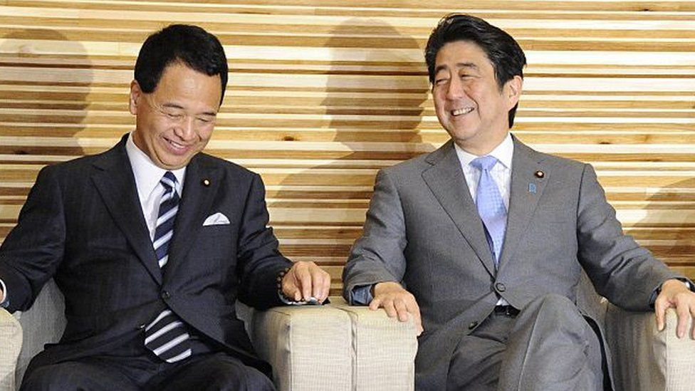 Japan's economy minister Akira Amari and Prime Minister Shinzo Abe