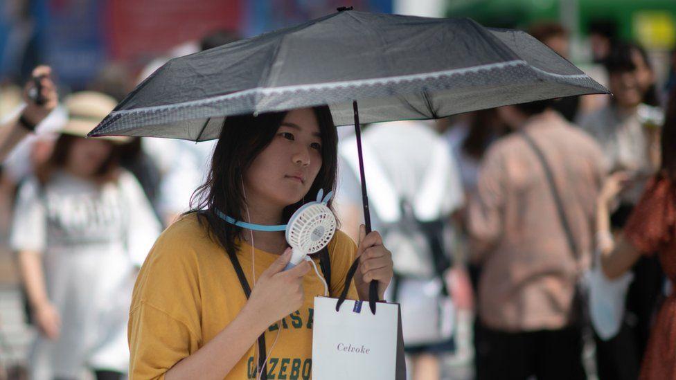 A woman fans herself in Tokyo.