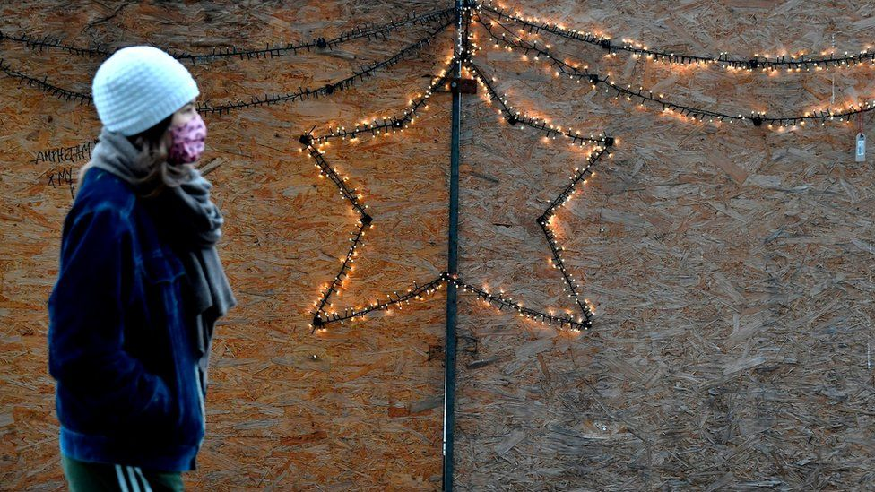 A woman in a face mask passes a Christmas decoration in Berlin, 16 December 2020