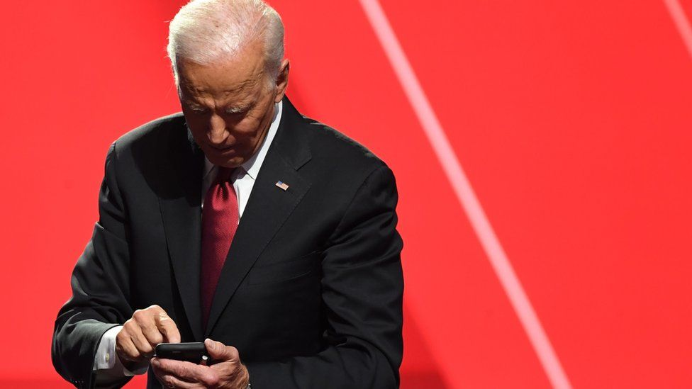 Joe Biden taps on a phone against a red backdrop in this 2019 file photo