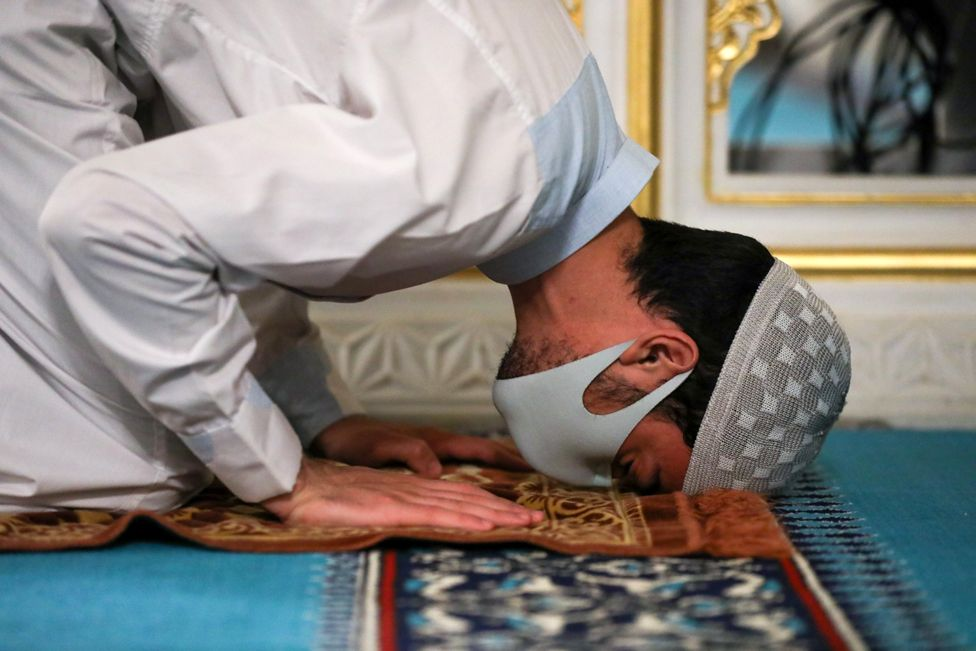 A Muslim worshipper prays whilst wearing a face mask
