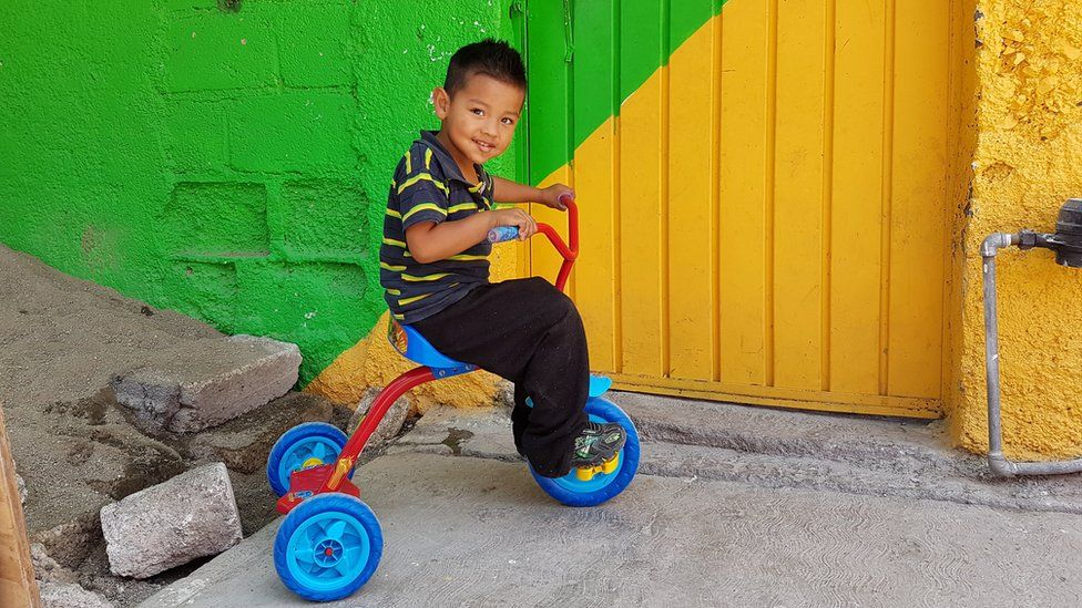 A boy rides a tricycle in Palmitas