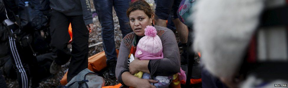 Migrant holding a child on Greek island of Lesbos, 10 November 2015